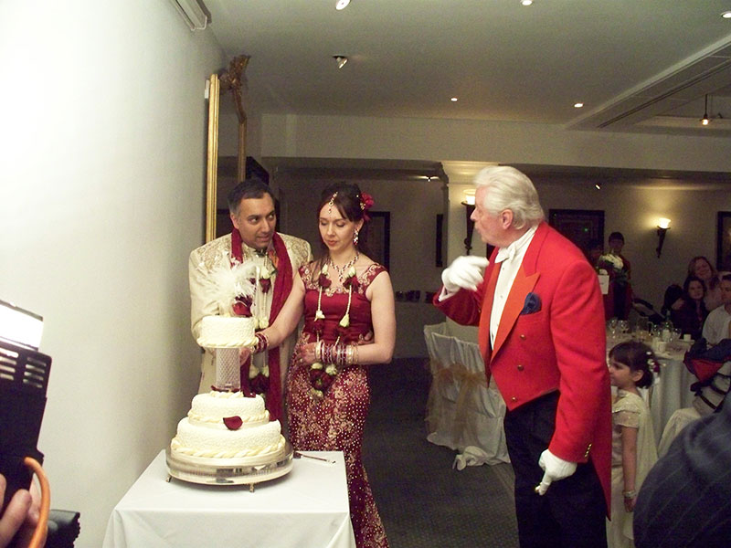 Toastmaster Assisting Cutting of Cake at Indian Wedding